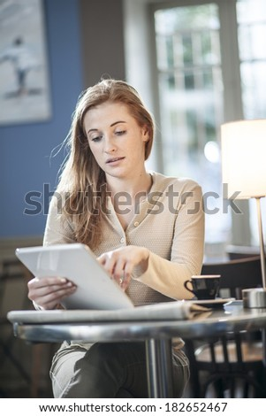 beautiful young woman sitting in a cafe and using a digital tablet - stock photo