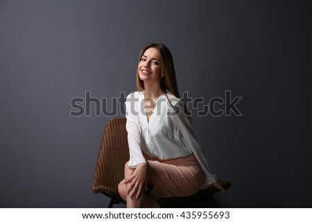 Beautiful young woman sitting in a chair on grey wall background - stock photo