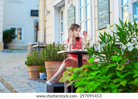 Beautiful young woman sitting in an outdoor cafe in Vienna, Austria and correcting her makeup - stock photo