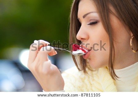 Beautiful young woman sitting in outdoor cafe eating a dessert - stock photo
