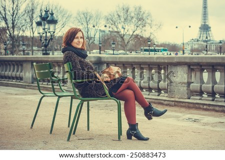 Beautiful young woman sitting in Paris overlooking the Eiffel Tower - stock photo