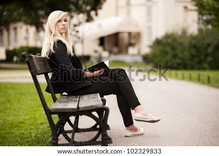 Beautiful young woman sitting in the park holding a book - stock photo