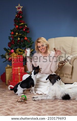 Beautiful young woman sitting near Christmas tree and shares his cookie with dog. - stock photo