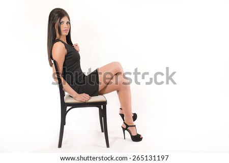 Beautiful young woman sitting on a chair with her legs crossed and looking seductively at the camera. She is wearing little black dress and sexy high heels. - stock photo
