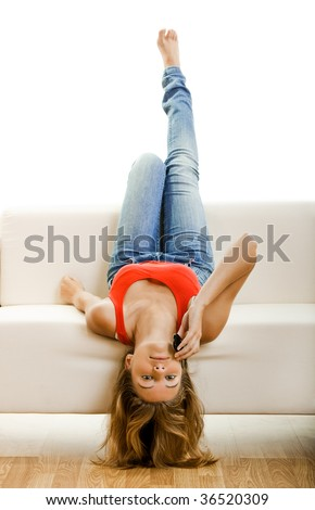 Beautiful young woman sitting on a couch and making a phone call - stock photo
