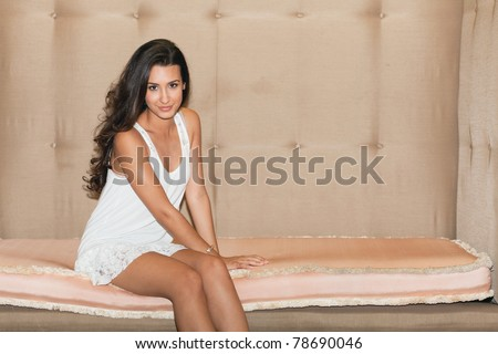 Beautiful young woman sitting on a large art deco sofa in a popular South Beach hotel in Miami Beach. - stock photo
