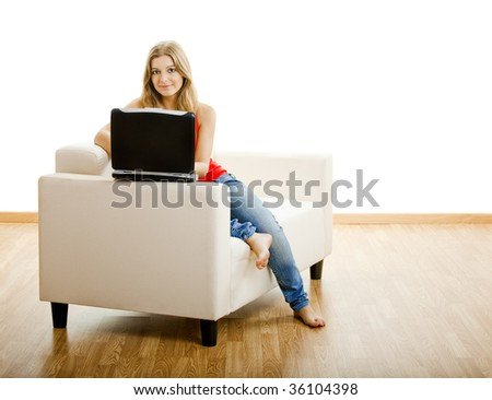 Beautiful young woman sitting on a sofa and working on a laptop - stock photo