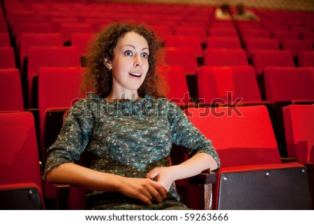 beautiful young woman sitting on armchairs at cinema, steadfastly looking - stock photo