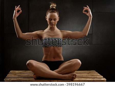 Beautiful young woman sitting on floor, practicing yoga eyes closed. - stock photo
