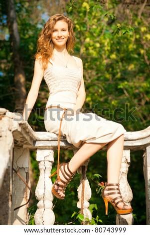 Beautiful young woman sitting on railing - stock photo