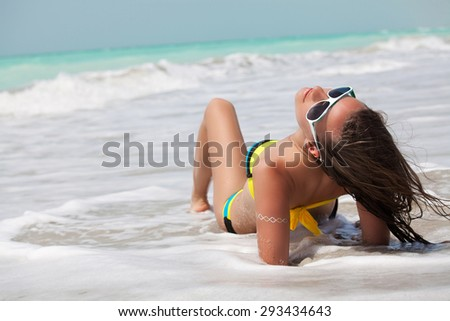 Beautiful young woman sitting on the beach in a bikini and enjoying the sunshine. Vacations And Tourism Concept. - stock photo