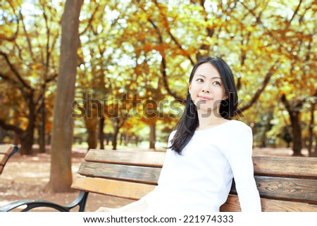 beautiful young woman sitting on the bench in autumn park - stock photo