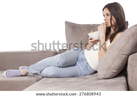 beautiful young woman sitting on the couch and eating chips  - stock photo