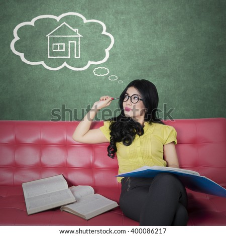 Beautiful young woman sitting on the sofa while reading books and dreaming a new house - stock photo