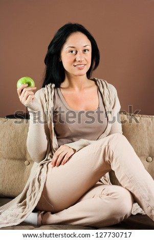Beautiful young woman sitting on the sofa with apple in her hand,Healthy snack - stock photo