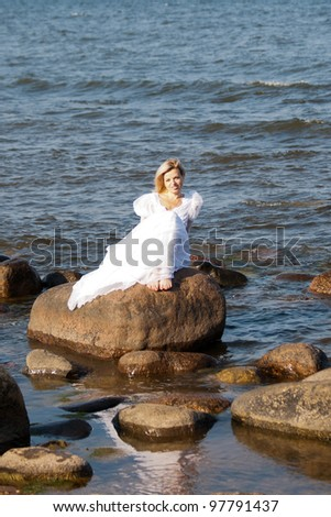 Beautiful young woman sitting on the stone on the seashore - stock photo
