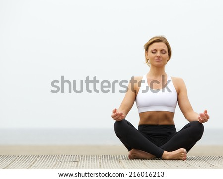 Beautiful young woman sitting outdoors in yoga pose - stock photo