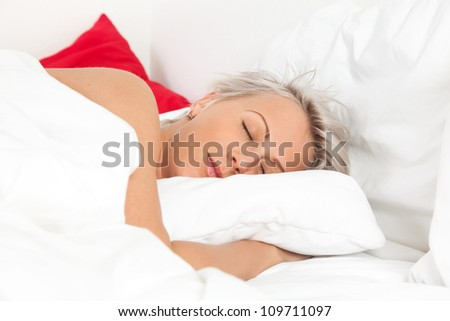Beautiful young woman sleeping in bed, over white - stock photo