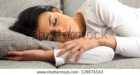 Beautiful Young Woman Sleeping On Sofa, Indoors - stock photo
