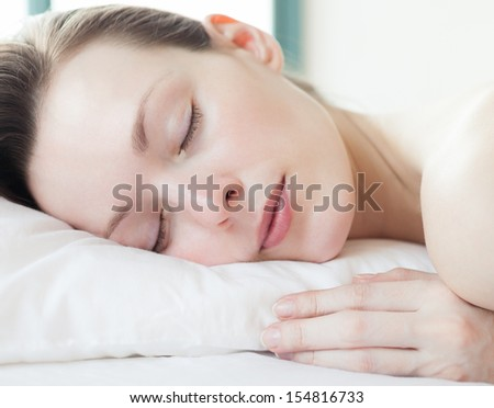 Beautiful young woman sleeps in the bedroom  - stock photo