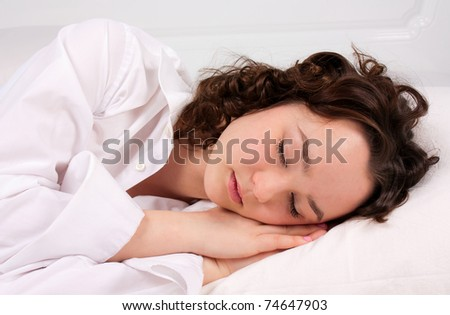 Beautiful young woman sleeps on the white bed - stock photo