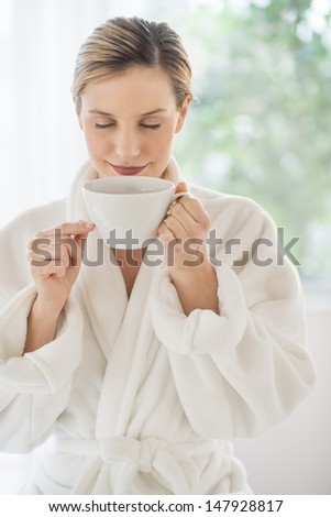 Beautiful young woman smelling cup of coffee in health spa - stock photo