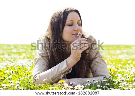 Beautiful young woman smelling flowers - stock photo