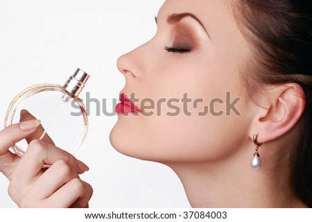 Beautiful young woman smelling her perfume - stock photo