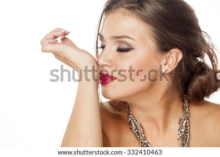 beautiful young woman smells perfume on her wrist - stock photo
