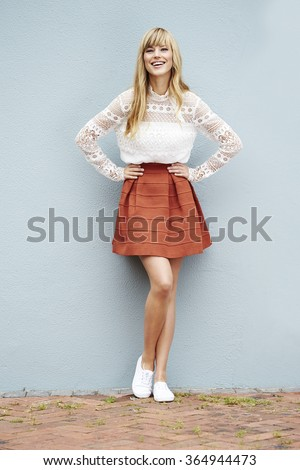 Beautiful young woman smiling against wall - stock photo