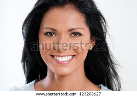 Beautiful young woman smiling and looking at camera on white background - stock photo