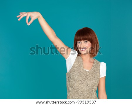 beautiful, young woman, smiling and pretending to hold something with her fingers, on blue background - stock photo
