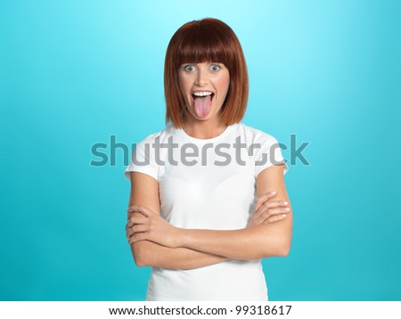 beautiful, young woman smiling and showing her tongue, on blue background - stock photo
