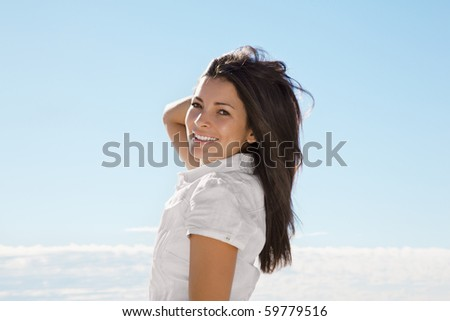 Beautiful young woman smiling at the beach - stock photo