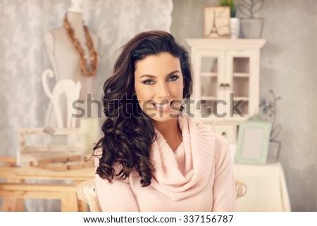 Beautiful young woman smiling at vintage home, looking at camera. - stock photo
