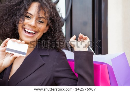Beautiful young woman smiling holding a credit card and colorful shopping bags - stock photo
