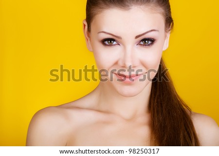 Beautiful young woman smiling isolated on yellow background - stock photo