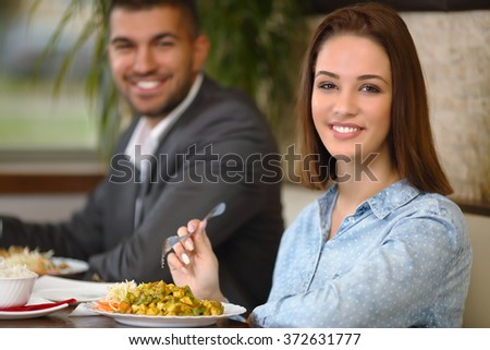 Beautiful young woman smiling to camera while having a dinner with her boyfriend at the restaurant - stock photo