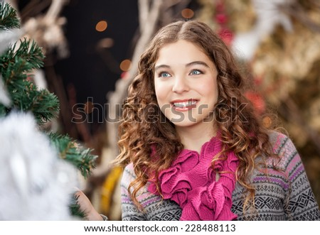 Beautiful young woman smiling while looking away in Christmas store - stock photo