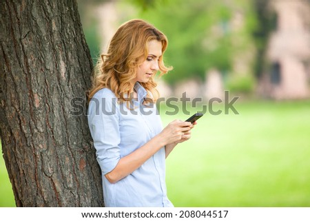 beautiful young woman speaking and texting on cellphone in a park with a happy mood - stock photo