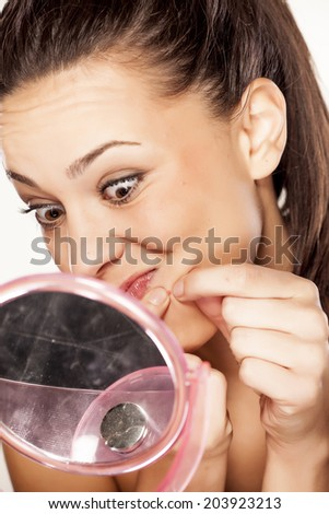 beautiful young woman squeezing pimples on her cheek - stock photo