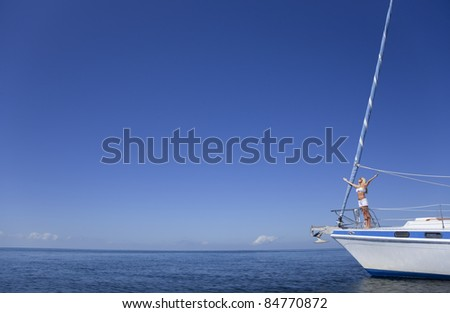 Beautiful young woman standing arms raised on the bow of a sail boat on a tranquil calm blue sea - stock photo