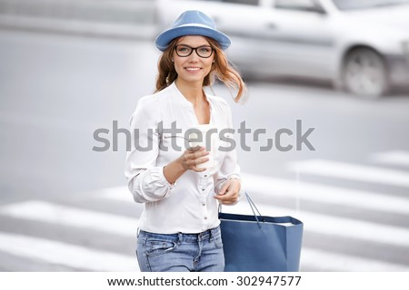Beautiful young woman standing at the crosswalk with a coffee-to-go cup, smiling happily against urban city background. - stock photo