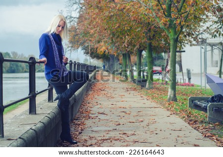 Beautiful young woman standing beside river on rainy autumn day. - stock photo