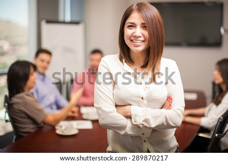 Beautiful young woman standing in a meeting room with a group of people working in the background - stock photo