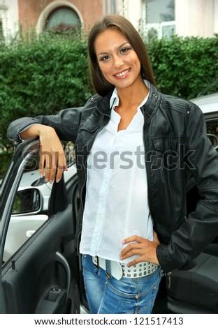 beautiful young woman standing near car - stock photo
