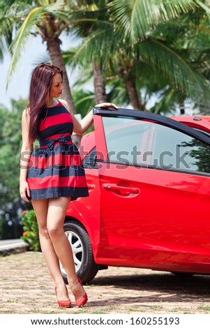 Beautiful young woman standing near red car. - stock photo