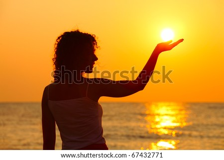 beautiful young woman standing on beach, watching sunset, holding  sun in hand - stock photo