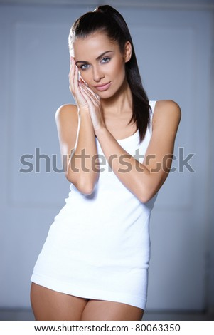 Beautiful young woman standing on grey background - stock photo