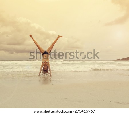 Beautiful young woman standing on hands on the beach - stock photo
